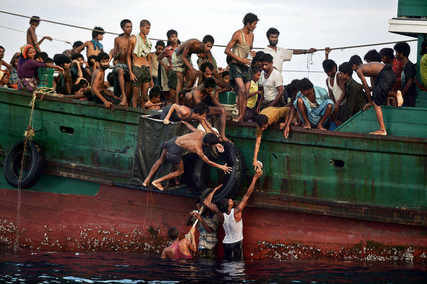 Rohingya migrants with airdropped food. A boat carrying them and scores of others, including young children, was found floating in Thai waters; passengers said several people had died.