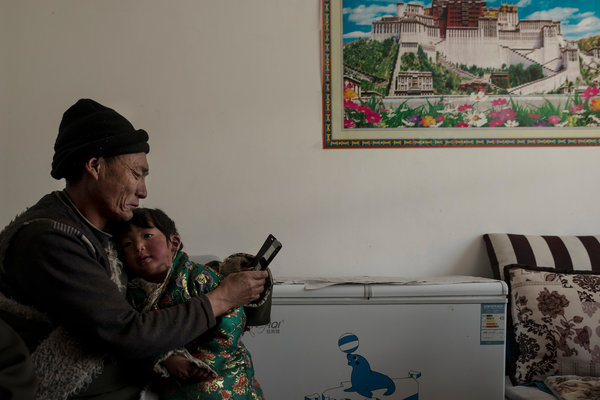 Gere, 59, an ex-herder in Qinghai, with his granddaughter. Forced to sell his herd and move into a house, he is jobless and in debt. CreditGilles Sabrie for The New York Times