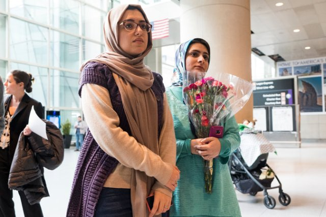 Sahar Harati, left, and Motahhare Eslami waiting for their parents to arrive at Logan Airport in Boston on Sunday. CreditM. Scott Brauer for The New York Times