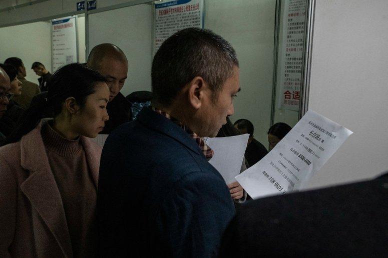上月,重庆,人们在招聘会上查看招聘信息。
