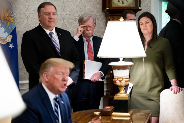 Secretary of State Mike Pompeo, top left, National Security Adviser John R. Bolton, center, and White House Press Secretary Sarah Huckabee Sanders, right, watching President Trump speak in the Oval Office on Thursday.