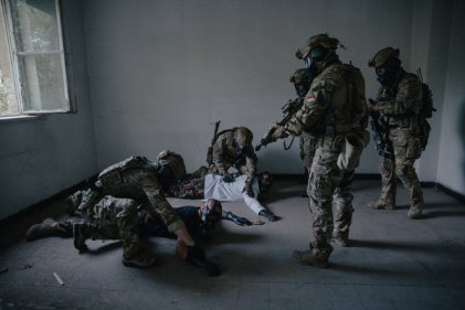 Hungarian commandos armed with M4 rifles and gas masks conducting a mock raid on an abandoned building where authorities suspected that notional Russian-backed Hungarian separatists were making a dirty bomb out of chlorine and other hazardous chemicals.