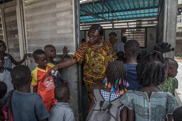 Pre-school principal Tirangue Doumbia ushering students into a new classroom built of recycled plastic bricks at the Gonzagueville school.