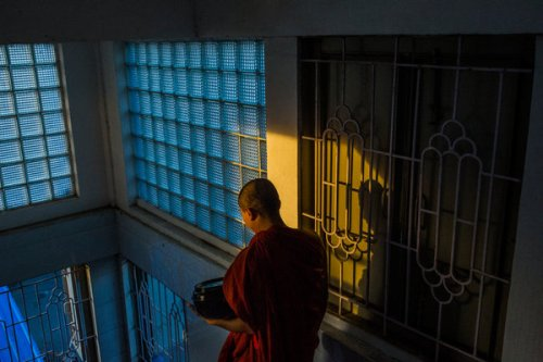 A Buddhist monk leaving the New Masoeyein monastery to collect alms, in Mandalay, Myanmar.