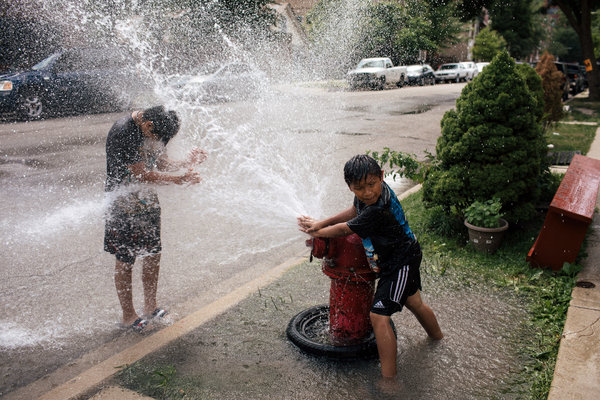 In Chicago, where temperatures reached the 90s on Friday, Peluche Mochen, 9, aimed a fire hydrant stream at Fernando Uribe, 11.