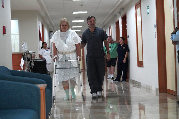 """Carlos Bauque, a physical therapist, helping Ms. Ferguson at Galenia Hospital. """"Even if I had to pay, I would come back here,"""" she said."""