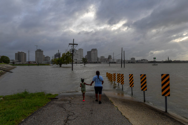 Charmiker Lewis, right, with Delmyree Stott, 6, along a flooded ramp on the Mississippi River walkway in New Orleans on Friday.