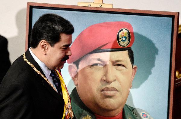 Nicolás Maduro, pasa frente a un retrato de su antecesor, Hugo Chávez.