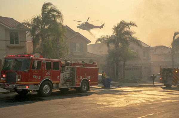 A helicopter dropped water onto a burning hillside in the Porter Ranch neighborhood.
