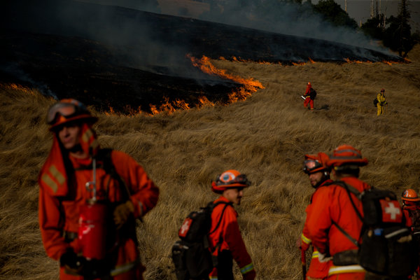 Firefighters lit backfires to help contain the Kincade fire in Geyserville, Calif., on Saturday.