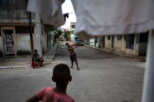 Unos niños juegan béisbol en La Habana.