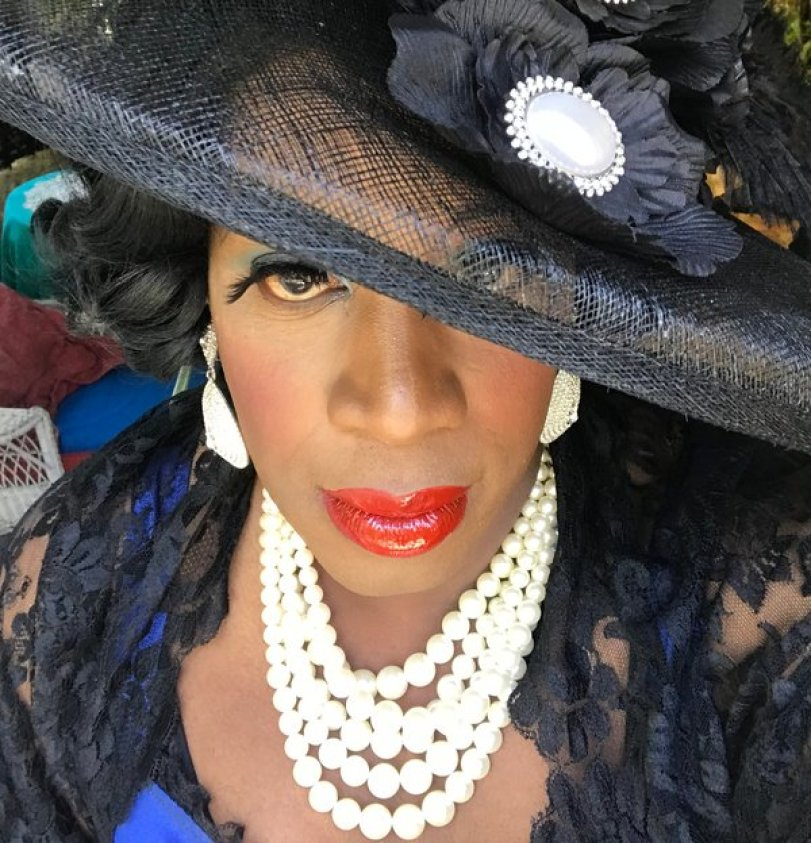 selfie of the artist as Désirée Josephine Duplantier with a big black hat, red lipstick, and pearls