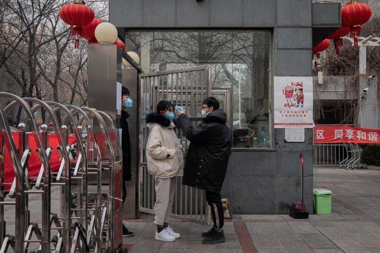 周一,北京一个社区保安正在对访客进行体温监测。