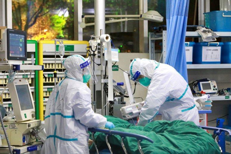 周二,身穿防护服的医护人员在武汉大学中南医院诊治一名新型冠状病毒确诊患者。