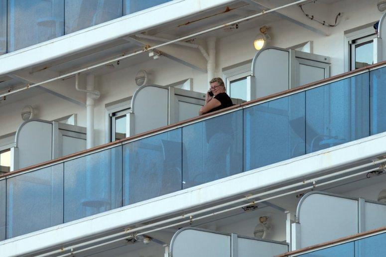 """一名乘客站在""""钻石公主号""""邮轮的阳台上,该邮轮在日本港口横滨隔离。船上的一些人感染了冠状病毒。"""