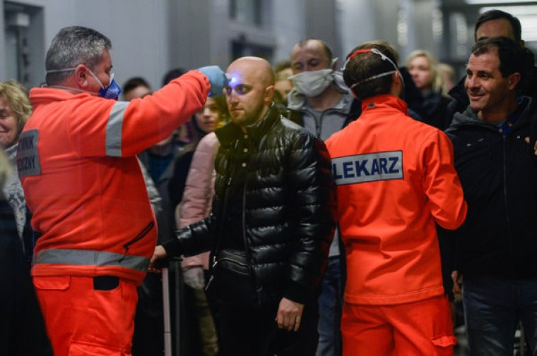 Health care workers screening the temperatures of passengers arriving at Krakow International Airport in Poland in February.