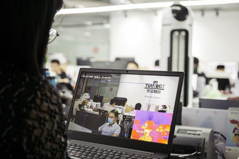 优艾智合机器人的一名员工演示了公司的杀毒机器人的体温监控功能。