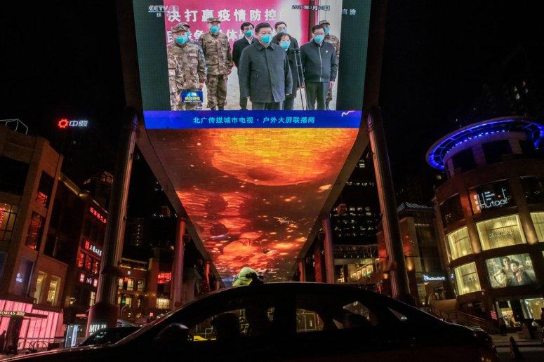 北京的一个大屏幕播放着中国领导人习近平视察武汉的新闻。大量的民族主义宣传将中国应对新冠病毒的做法描述为其他国家的榜样。