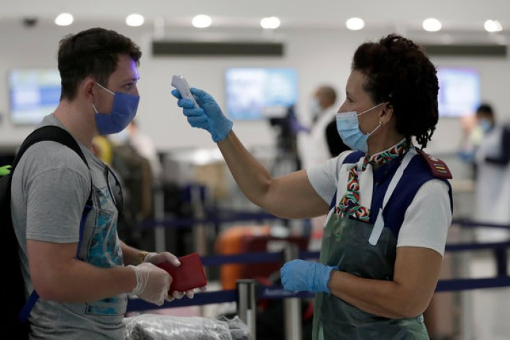 Rosemary Arends, right, a nurse and flight attendant for South African Airways, checking the temperature of a passenger before a charter flight from Miami International Airport.