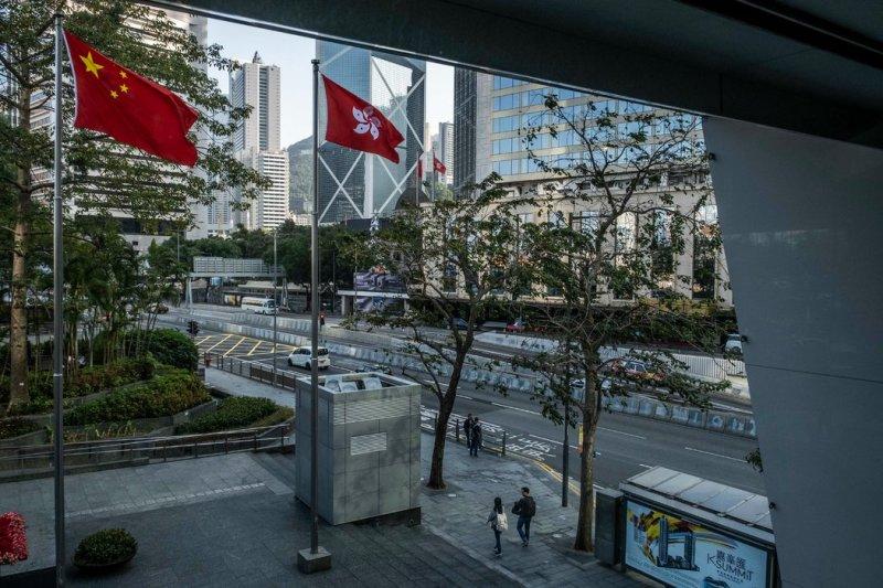 在香港商业区并排飘扬的中国国旗和香港特别行政区区旗。