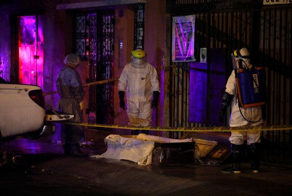 Funcionarios del Ministerio de Salud rodean un cadáver que alguien dejó en una acera de Lima.