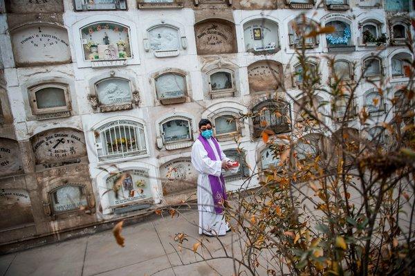 Un sacerdote en el cementerio de El Ángel antes del funeral de una víctima de la COVID-19 en Lima.