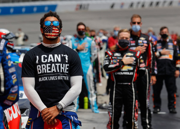 "Bubba Wallace wears an ""I Can't Breath/Black Lives Matter"" T-shirt during the national anthem before a race at Atlanta Motor Speedway this month."