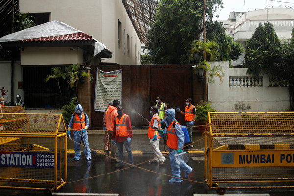 Municipal workers waiting on Sunday to enter the Bachchan family residence in Mumbai to sanitize it.