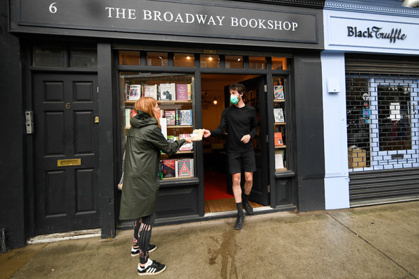 Handing off an order to a customer outside a bookshop in London, last month. The economic outlook for the rest of this year in Britain remains bleak.