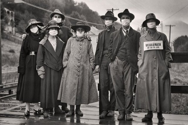 "Rail commuters wearing white protective masks, one with the additional message ""wear a mask or go to jail,"" during the 1918 influenza pandemic in California."