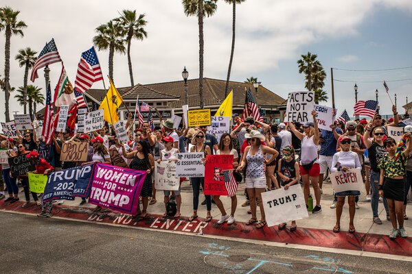 Protesters demonstrated against the state's stay-at-home order at the entrance to the Huntington Beach Pier.