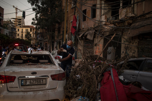 Security: A resident checking his car, destroyed in the blast.