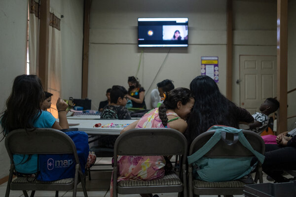 Two students laugh together during a virtual class at the church and migrant shelter in Tijuana, Baja California State, in August.