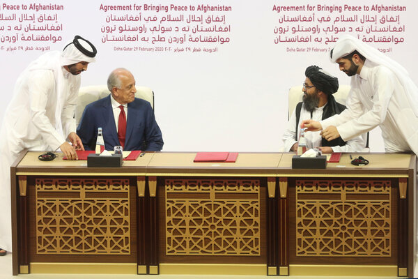 The United States negotiator Zalmay Khalilzad, left, and Mullah Abdul Ghani Baradar, a founding leader of the Taliban, signing the Feb. 29 peace agreement in Doha, Qatar.