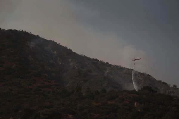 Firefighters battle the Bobcat Fire in Arcadia, Calif. on Monday.