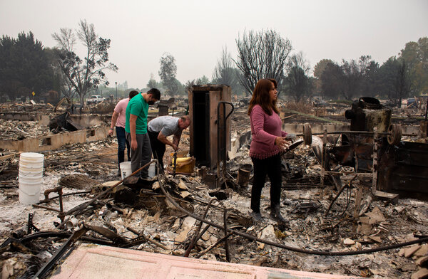 """Kirt and Dimna Meyer search through the rubble of their home in Phoenix, Ore., on Monday with their sons. """"Everything was here,"""" Dimna said. """"We had just paid off the house and now we lost everything."""""""