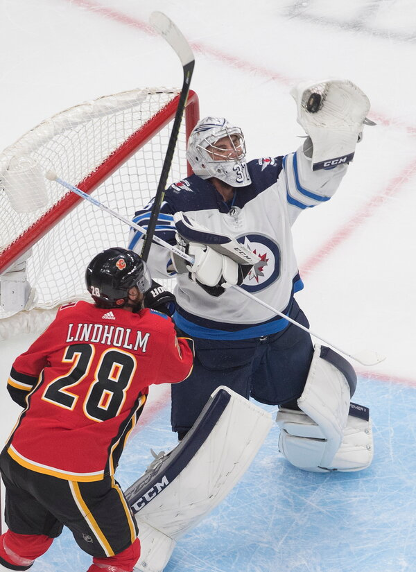 The Jets' Connor Hellebuyck, right, faced more shots than any other goalie during the regular season.