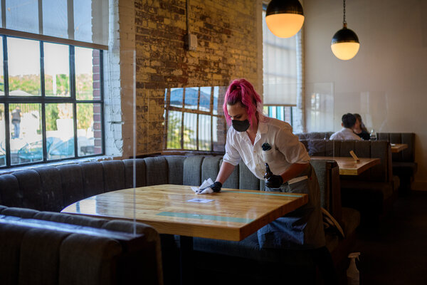 Lacy Kowalkowski sanitizes a table at Pinewood Social in Nashville. Restaurants are predicting more layoffs as outdoor dining declines with the arrival of cooler weather.