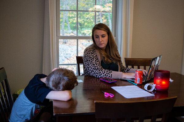 MacKenzie Nicholson helping her 7-year-old with his schoolwork. She lost her job in June, and the family is struggling to get by on her unemployment benefits and her husband's income.