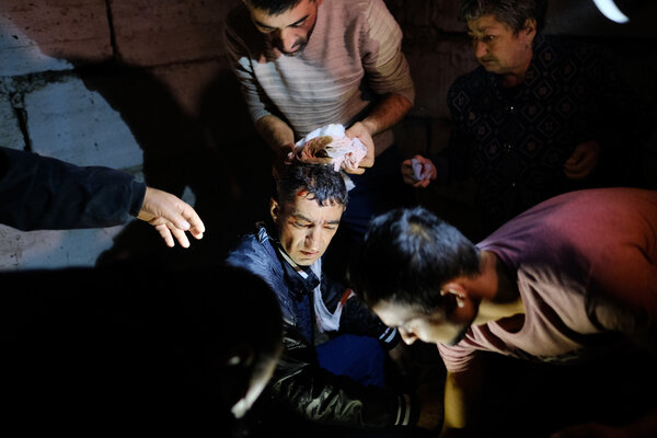 People tended to an injured man in a bomb shelter during shelling in Stepanakert on Sunday.