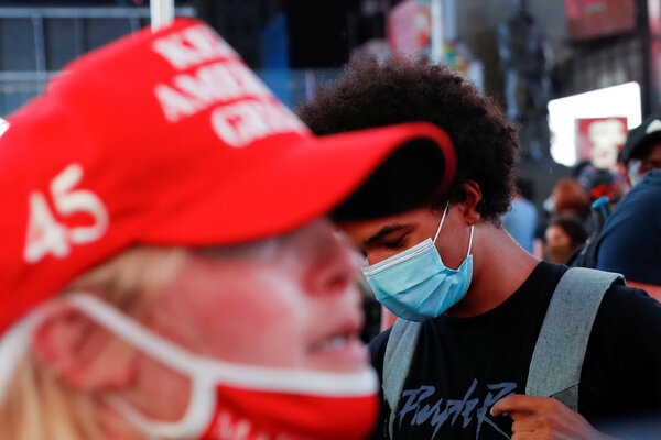 A supporter of U.S. President Donald Trump is seen as a demonstrator wearing a face mask at Times Square in New York.