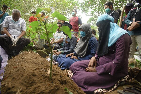 Haresa, second from right, at the burial of her sister, who died two days after their boat landed in Aceh.