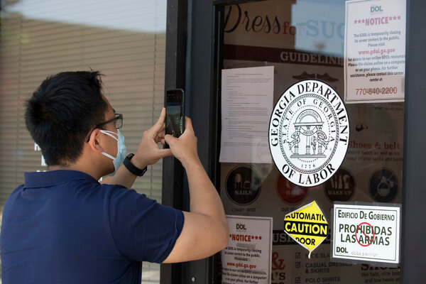 A man uses his phone to copy phone numbers posted on the locked doors of a Georgia Department of Labor office.