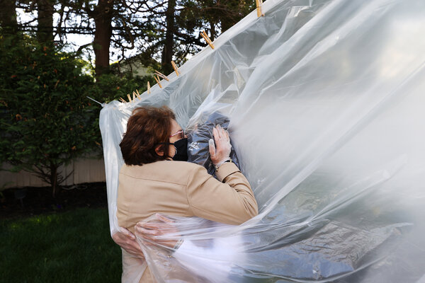 Michelle Grant (R) hugs her mother, Mary Grace Sileo through a plastic drop cloth during Memorial Day Weekend.