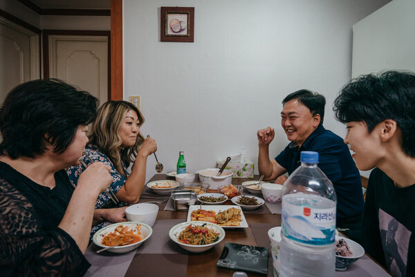 "Ms. Guy, second from left, sharing dinner with her birth family at her parents' apartment. ""I didn't get to feed my daughter for 33 years, so this is the least I could do,"" said Lim Mi-soon, 59, Ms. Guy's birth mother."