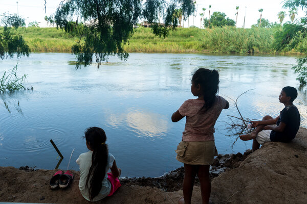 Children playing on a bank of the Rio Grande across from Brownsville, Texas.