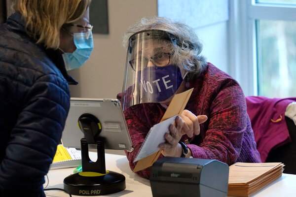 Alice Machinist of Newton, Mass., wears a mask and face shield while working at the polls assisting a voter with a ballot during early in-person voting.