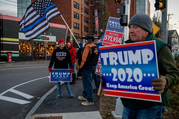 A group of people wave flags in support of President Trump's re-election.