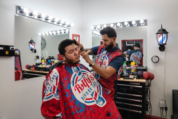 Rolfy Bueso cutting the hair of Francisco Barrera at one of two barbershops Bueso owns in Chamblee.