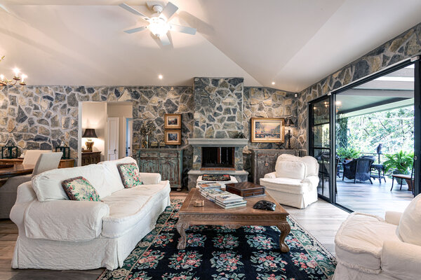 The great room has stone walls, a vaulted ceiling, and a floor-to-ceiling, double-sided stone fireplace. Sliding glass doors open to a covered terrace.